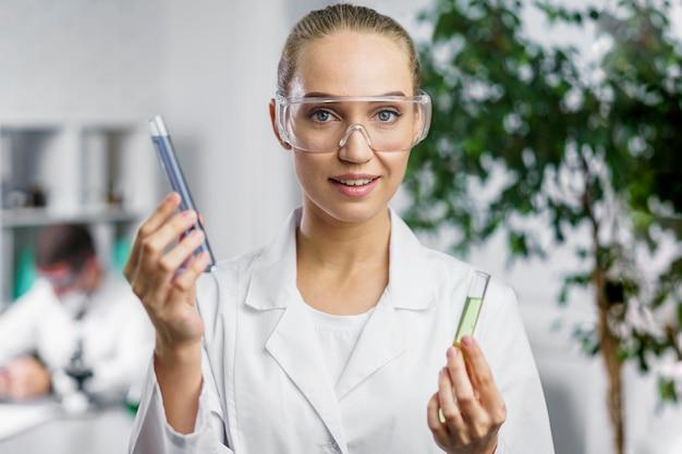 Retrato de pesquisadora em laboratório com óculos de segurança e tubos de ensaio