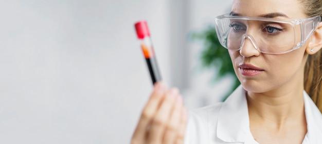 Retrato de pesquisadora em laboratório com tubo de ensaio e espaço de cópia