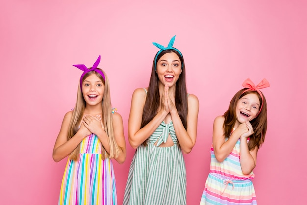 Retrato de pessoas alegres com bandanas gritando uau e ouvindo notícias usando saia vestido colorido isolado sobre fundo rosa