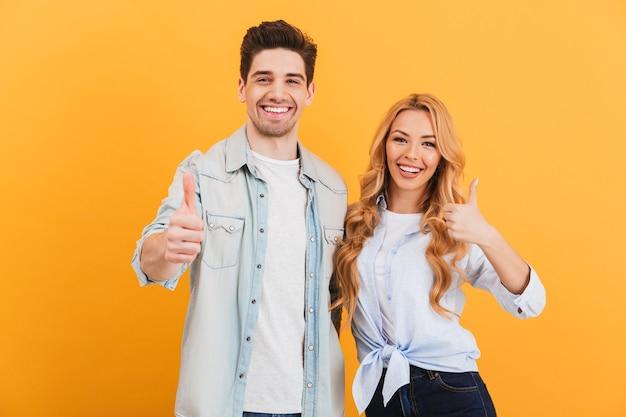 Retrato de pessoas alegres, homem e mulher em roupas básicas, sorrindo e mostrando os polegares para cima