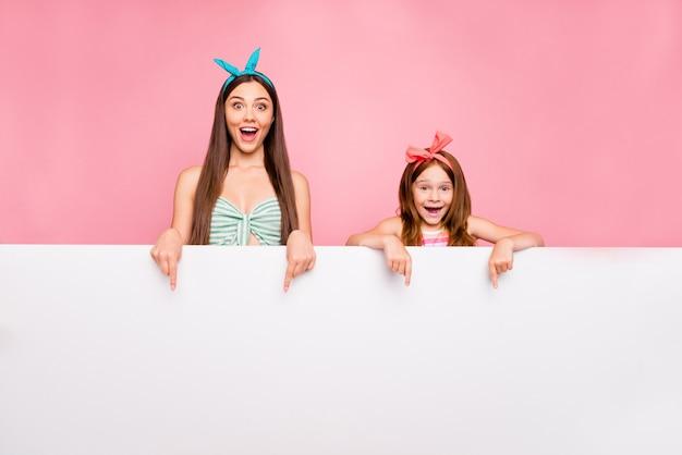 Retrato de pessoas chocadas com cabelo ruivo morena gritando uau show com promoção de dedo indicador usando bandanas isoladas sobre fundo rosa
