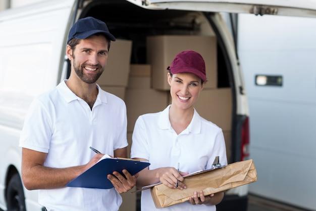 Retrato de pessoas de entrega estão segurando mercadorias e sorrindo para a câmera
