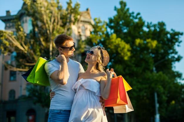 Retrato de pessoas felizes com marido e mulher grávida fazendo compras em uma rua da cidade