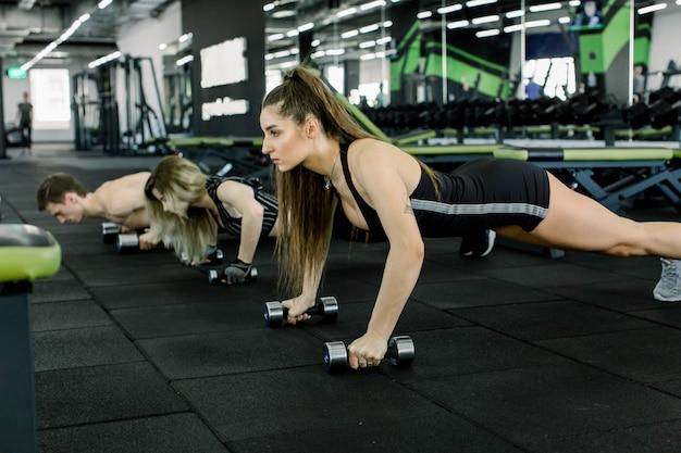 Retrato de pessoas jovens de aptidão fazendo levantando o exercício com halteres no ginásio. estilo de vida das pessoas e conceito de esporte. três amigos segurando o peso por duas mãos no chão.