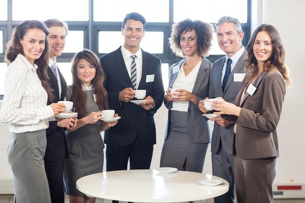 Retrato, de, pessoas negócio, ficar, junto, e, sorrindo, em, escritório, durante, breaktime
