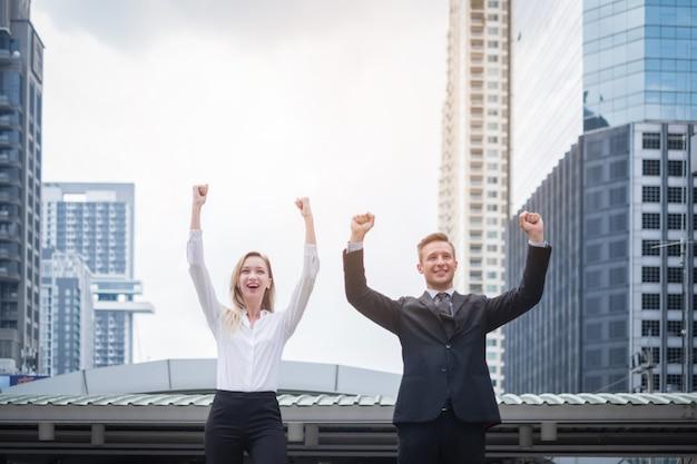 Retrato, de, pessoas negócio, sorrindo, com, braços cima, celebrando, vitória, ao ar livre