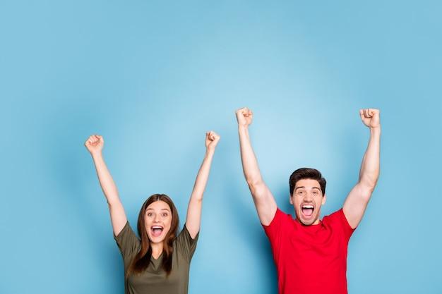 Retrato de positivo louco duas pessoas mulher homem tem sorte ganhar na loteria levantar punhos gritar sim usar roupas de estilo casual isoladas sobre fundo de cor