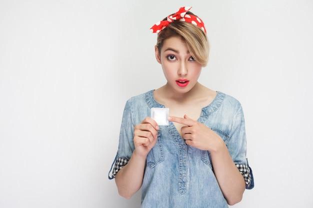 Retrato de preocupação linda jovem em camisa jeans casual e bandana vermelha em pé, segurando a camisinha e apontando o dedo com cara de perguntar. tiro de estúdio interno, isolado no fundo branco