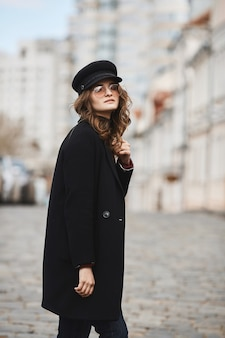 Retrato de primavera ao ar livre de jovem elegante na moda, óculos da moda, casaco vermelho e chapéu, andando em uma rua de uma cidade europeia.