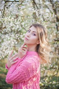 Retrato de primavera de uma jovem loira perto de uma árvore florida. mulher jovem feliz. primavera.