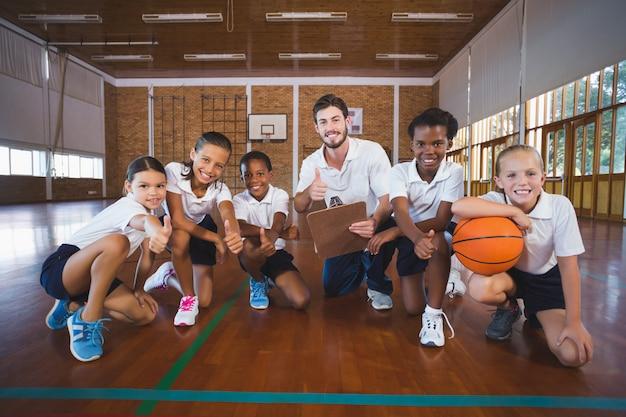 Retrato de professor de esportes e crianças da escola na quadra de basquete