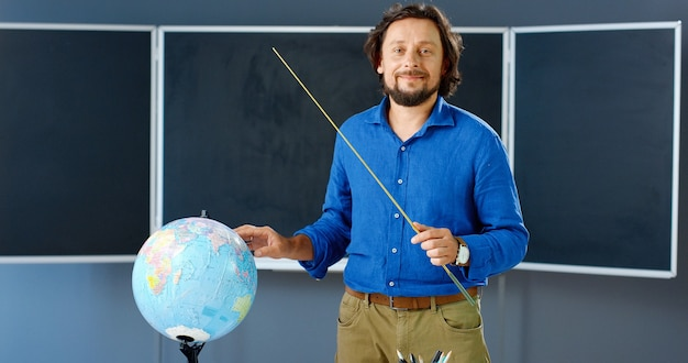 Retrato de professor do sexo masculino caucasiano em pé na placa com o ponteiro e apontando no globo em classe. homem ensinando geografia em sala de aula. aula online. palestrante explicando o tema.