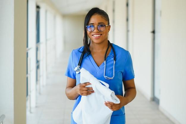 Retrato de profissional de saúde feminino confiante, sorridente e amigável com jaleco, braços cruzados segurando os óculos. fundo de clínica hospitalar isolado.