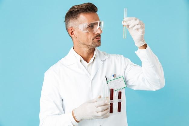 Retrato de profissional médico usando óculos segurando tubos de ensaio com sangue, isolado na parede azul