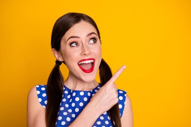 Retrato de promotor de menina positiva surpreso indica promoção de anúncios incrível grito impressionado usar roupas de bolinhas com boa aparência isolado fundo de cor brilhante brilhante