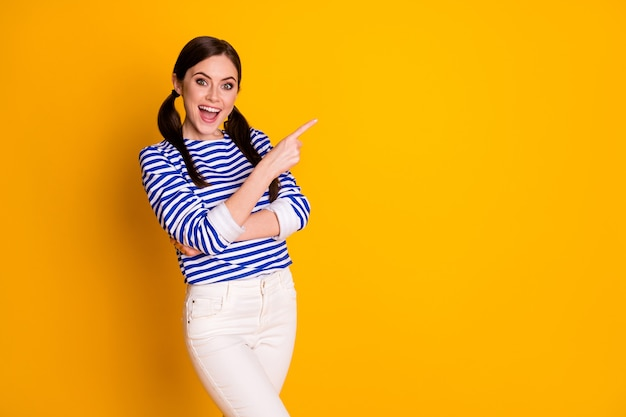 Retrato de promotor positivo alegre e animado ponto dedo indicador copyspace recomendar sugerir selecionar anúncios promo vestir roupas de boa aparência isolado fundo de cor brilhante