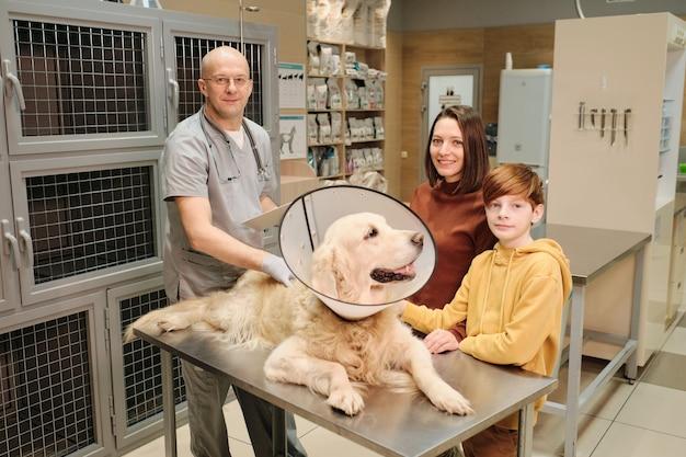 Retrato de proprietários sorrindo para a câmera em pé na clínica veterinária enquanto o médico examina seu cachorro