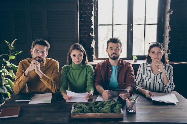 Retrato de quatro agradáveis recrutadores profissionais qualificados e ocupados reunindo-se com um candidato a emprego
