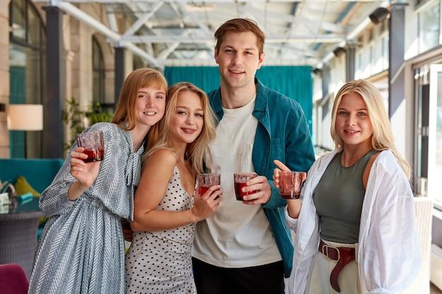 Retrato de quatro amigos caucasianos com copos de bebidas