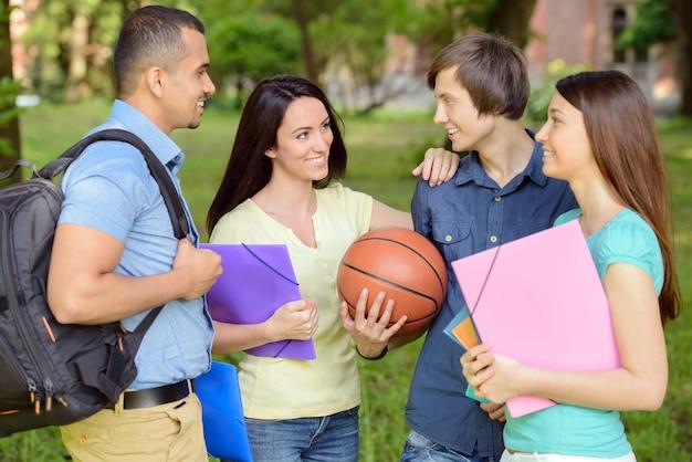 Retrato de quatro estudantes alegres de sorriso ao ar livre no parque.