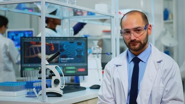 Retrato de químico exausto, olhando para a câmera no moderno laboratório equipado. equipe multiétnica examinando a evolução do vírus usando ferramentas químicas e de alta tecnologia para pesquisa científica e desenvolvimento de vacinas.