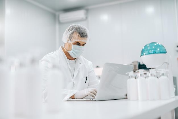 Retrato de químico sério com máscara, luvas de borracha, rede de cabelo e uniforme estéril, trabalhando no laptop no laboratório