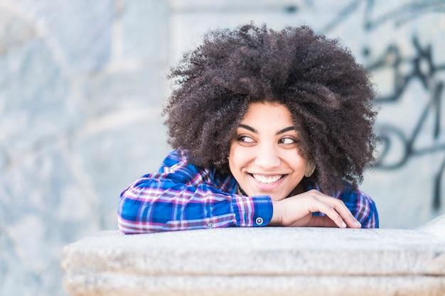 Retrato de raça africana de pele negra de linda jovem sorrindo e olhando para o lado dela