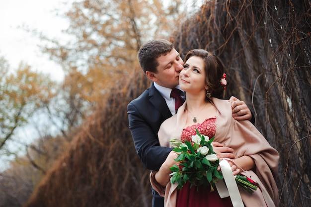 Retrato de recém-casados felizes na natureza outono. noiva e noivo felizes abraçando e beijando