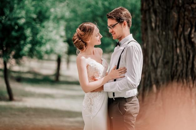 Retrato de recém-casados felizes no fundo do parque primavera