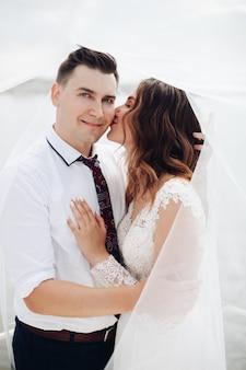 Retrato de recém-casados se abraçando e sorrindo junto com um véu de noiva ao redor deles