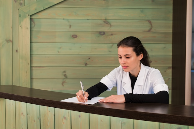 Retrato de recepcionista feminina, explicando o formulário para o paciente na clínica de dentista