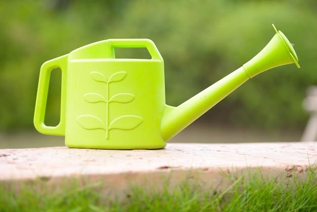 Retrato de regador de plástico verde no quintal