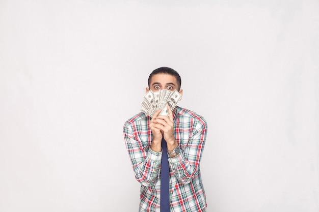 Retrato de rico empresário jovem e bonito em camisa quadriculada colorida com gravata azul em pé e mostrando leque de dólares com olhos grandes e malucos. interior, estúdio tiro, isolado em fundo cinza.