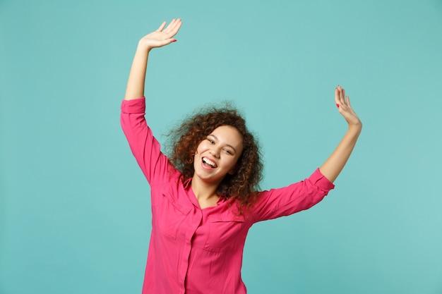 Retrato de rir alegre menina bonita africana em roupas casuais, levantando as mãos isoladas no fundo da parede azul turquesa no estúdio. emoções sinceras de pessoas, conceito de estilo de vida. simule o espaço da cópia.