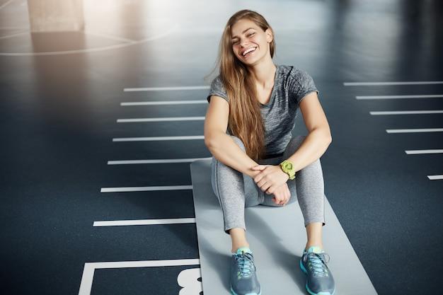 Retrato de rir jovem instrutor de fitness feminino sentado no espaço vazio, após um treino longo e duro. conceito de aptidão.