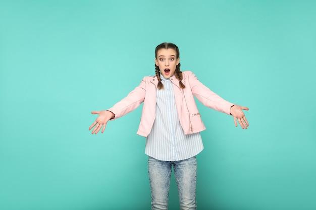 Retrato de rosto chocado espantado de linda linda garota em pé com maquiagem e penteado pigtail marrom em jaqueta listrada de camisa azul claro rosa. indoor, studio shot isolado em fundo azul ou verde.
