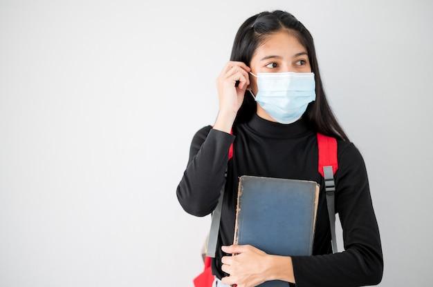 Retrato de rosto de close up estudantes universitárias asiáticas usam máscara e mantêm distâncias sociais durante o horário escolar.