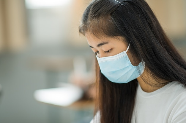Retrato de rosto de closeup estudantes universitárias asiáticas usam máscara e mantêm distâncias sociais durante o horário escolar.
