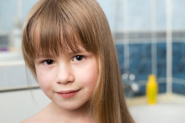 Retrato de rosto de menina bonita, criança sorridente com belos olhos e cabelo loiro muito molhado no borrado do banheiro.