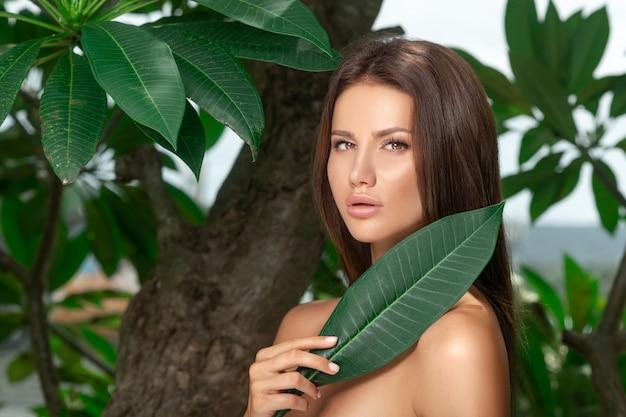 Retrato de rosto de mulher bonita com folha verde, cuidados com a pele ou cosméticos orgânicos