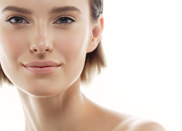 Retrato de rosto de mulher bonita conceito de cuidados com a pele de beleza bela beleza jovem modelo feminino tocando sua pele do rosto bochechas mãos dedos. moda beleza modelo isolado no branco