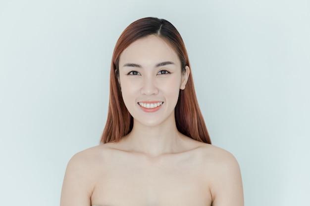 Retrato de rosto de mulher de beleza. menina bonita do modelo dos termas com pele limpa fresca perfeita. fêmea moreno que olha a câmera e o sorriso. conceito de juventude e cuidados com a pele