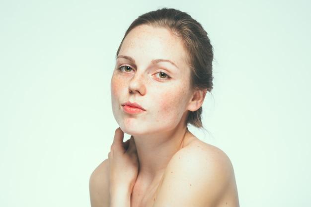 Retrato de rosto de mulher linda sardas de ombros nus. fundo azul.