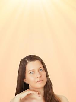 Retrato de rosto ensolarado de jovem bronzeado de sol e cosméticos de beleza linda morena modelo feminino com bronzeado natural usando protetor solar