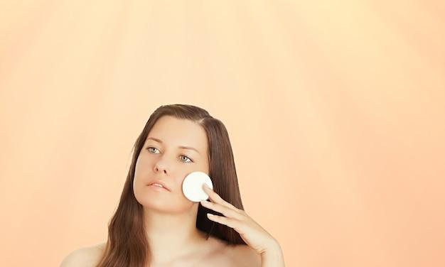 Retrato de rosto ensolarado de jovem bronzeado de tom de pele e cosméticos de beleza linda morena modelo feminino com bronzeado natural usando protetor solar