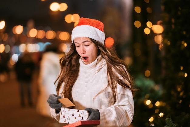 Retrato de rua à noite de uma jovem mulher bonita agindo emocionado. luzes festivas de guirlanda.