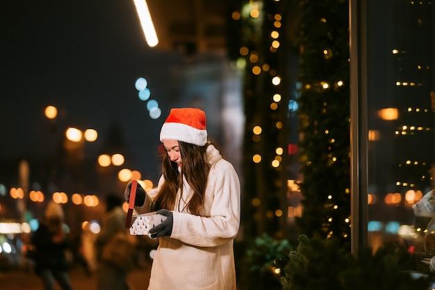 Retrato de rua à noite de uma jovem mulher bonita agindo emocionado. luzes festivas de guirlanda. Foto gratuita