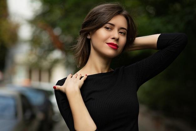 Retrato de rua de moda de uma mulher bonita morena com lábios vermelhos usa um vestido preto elegante, andando pela cidade de outono. espaço para texto