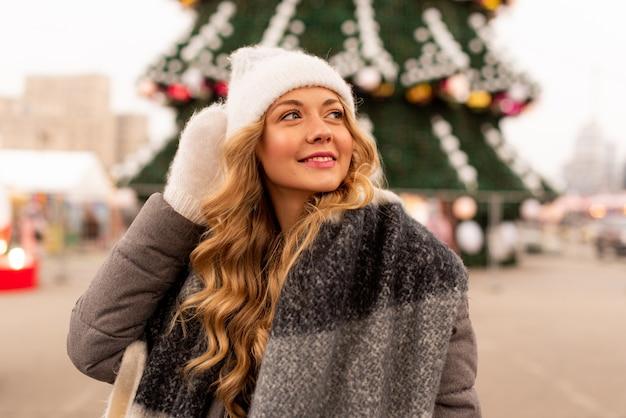 Retrato de rua de mulher jovem e bonita sorridente na festiva feira de natal. menina usando luvas de malha elegantes de inverno e segurando pirulito.