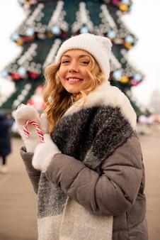 Retrato de rua de mulher jovem e bonita sorridente na festiva feira de natal. menina usando luvas de malha elegantes de inverno.